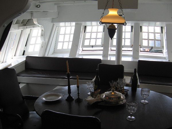 Photo inside the great cabin of HMS Surprise. In real life the space feels cramped and the table is small. The large stern windows are a familiar sight in the movie.
