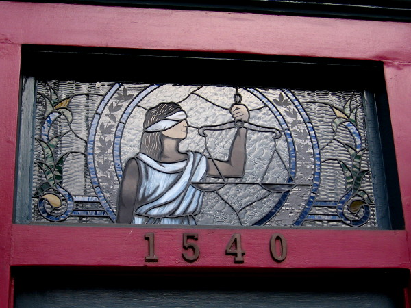 A beautiful window above the entrance of Sidiropoulos Law Firm on Sixth Avenue depicts blind Justice holding her scales.