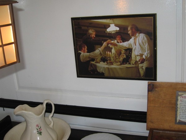 Photo on wall recalls a scene in Master and Commander. Captain Jack Aubrey shares a toast with ship's doctor and officers.