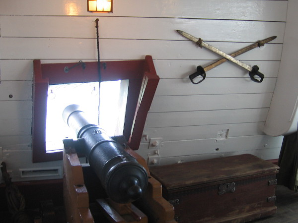 Gun on the starboard side of the great cabin, next to a chest and swords hung at the ready in case the ship was boarded by the enemy, or sailors mutiny.