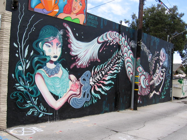 A cool Pangea Seed Foundation Sea Wall created in North Park by Lauren YS. A beautiful underwater mermaid is contrasted with a skeleton.