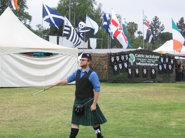 A Scottish drum major practices on the field, with flags flying in the background.