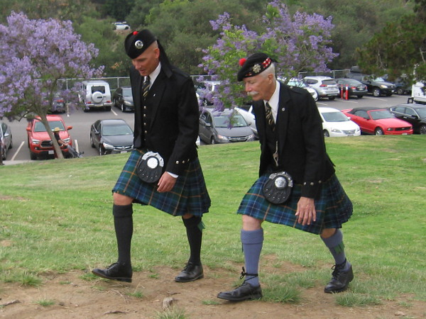 Two gents stride across the grass to another area of the park, where pipe bands, drummers and bagpipers compete.