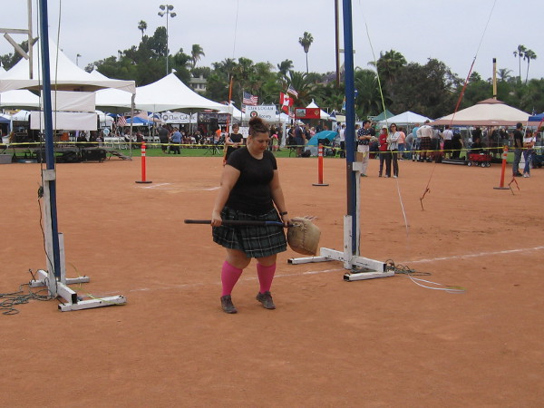 A female contestant readies to toss the sheaf with a pitchfork.