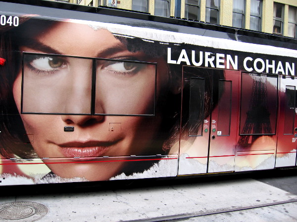 A trolley wrap for 2018 Comic-Con promotes ABC's upcoming drama Whiskey Cavalier. Lauren Cohan costars with Scott Foley. Both are CIA operatives.