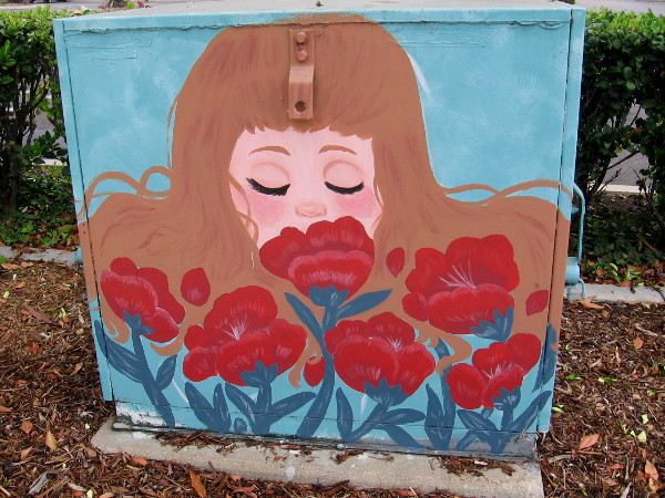 Artwork painted on an electrical box at Rio Vista depicts a lady smelling red flowers.
