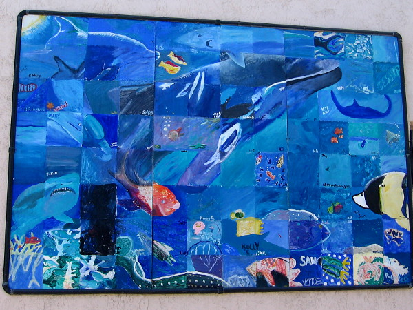 A whale, shark, dolphin, ray and other sea life painted on a community mural in Ocean Beach.