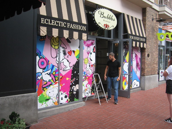 Snoopy graphics on the windows of Bubbles Boutique transform it into the Peanuts Pop-Up Shop!