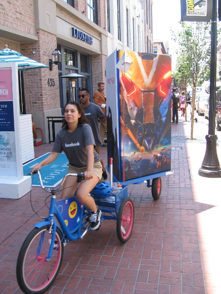 Here comes a small mobile billboard towed by a bicycle. Cool graphic, whatever the heck you're promoting.
