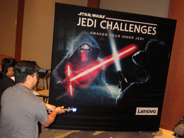Someone engages in an augmented reality lightsaber battle courtesy of Star Wars Jedi Challenges by Lenovo.