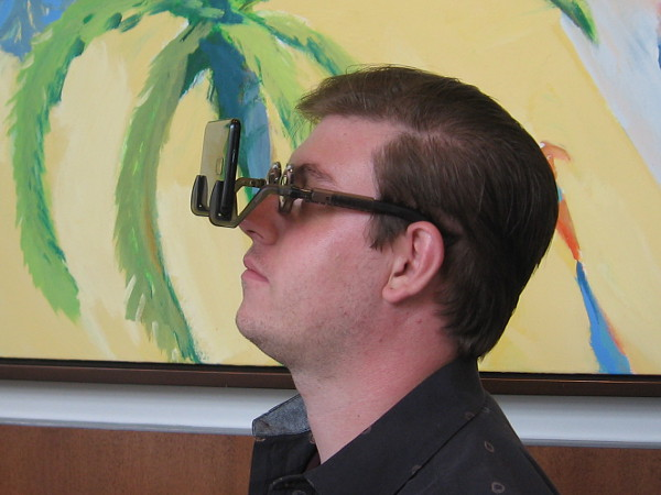 A friendly guy representing Stimuli VR demonstrates glasses that convert almost any smart phone into a virtual reality device!