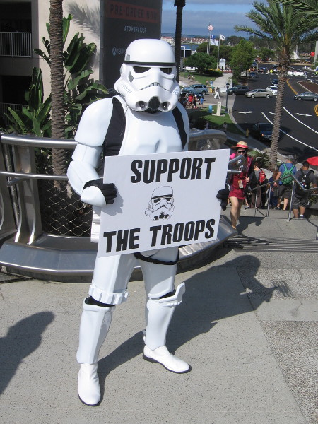 A Star Wars stormtropper holds a humorous sign. Support the Troops.