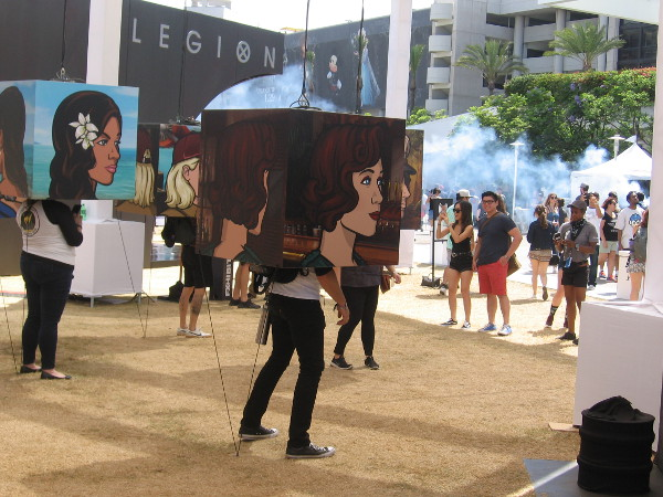 People place their heads in Archer character cubes for an unusual photo opportunity.
