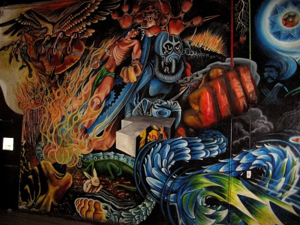 Tezcatlipoca, jaguar, god of night, war and destruction, dominates the dark, violent left section of the large mural inside Centro Cultural de la Raza.