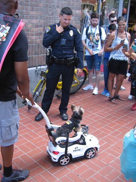 A dog in a tiny police car meets a real officer of the SDPD.