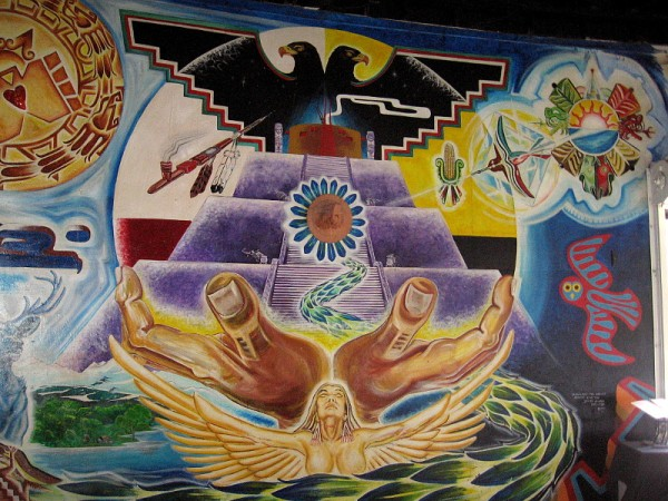 Quetzalcoatl, feathered serpent, wise creator of humankind, moves through the mural and finally faces the viewer from the center of a pyramid, amid symbols of life and light.