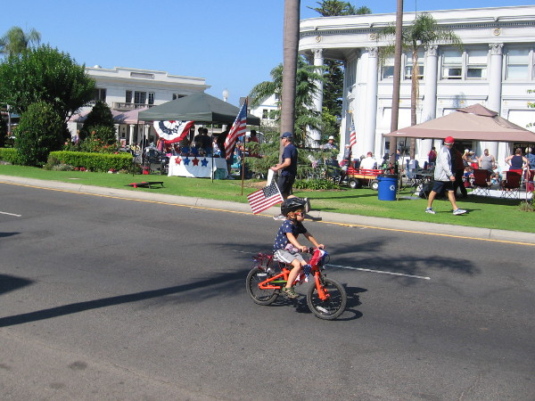Kid heads down Orange Avenue on a small bicycle decorated for Independence Day.