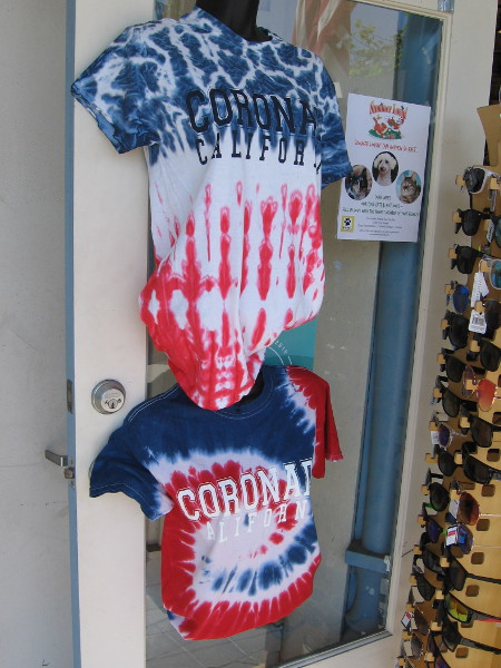 These tie-dye Coronado shirts in front of a shop are red, white and blue.