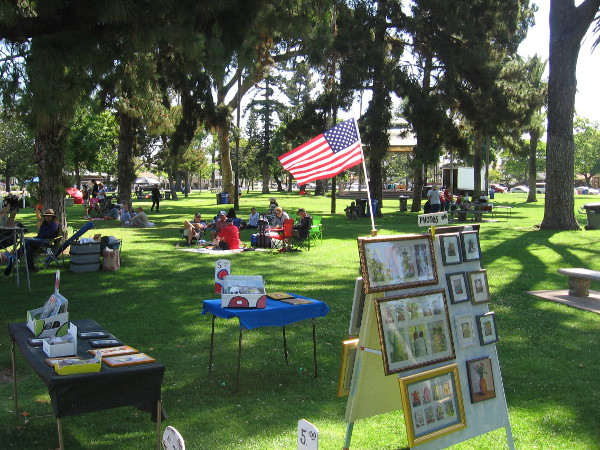 People relax and look at artwork for sale in Spreckels Park. An afternoon concert in the park features patriotic music.