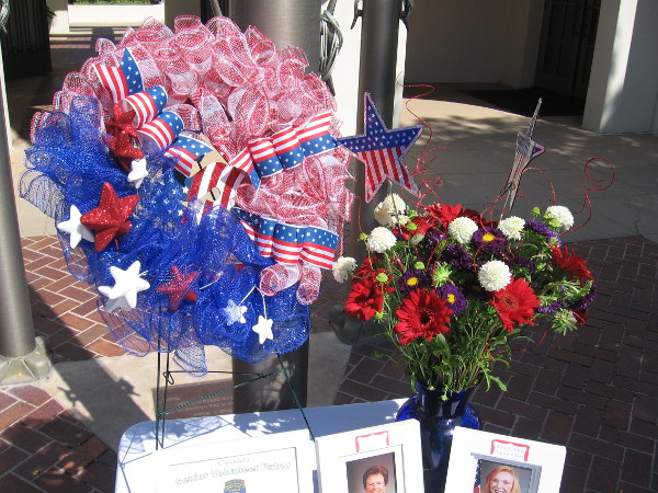 Patriotic wreath and bouquet in front of the Coronado Police headquarters honor and remember Senior Volunteer Patrol volunteers who recently passed away.