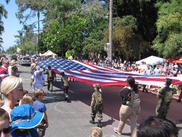 A big American flag carried by many hands.