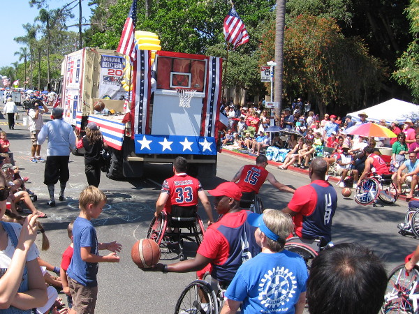 Guys in wheelchairs shoot hoops behind the Rotary float.