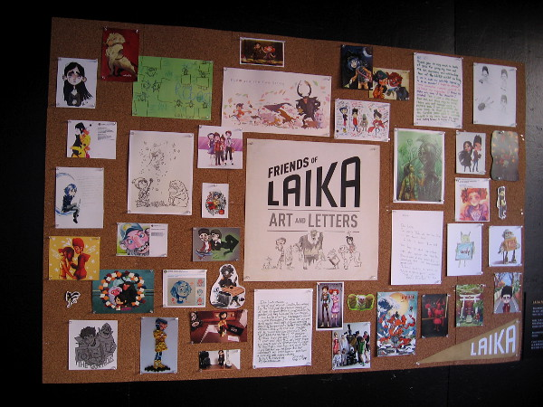 A board contains Laika fan art and letters.
