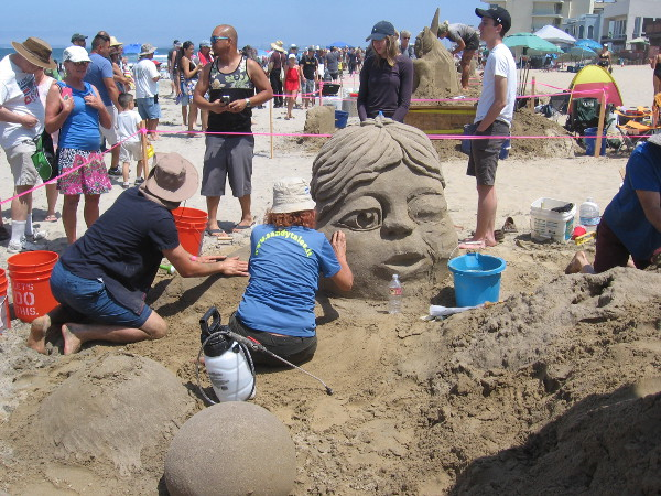 Sandytales was creating Dreaming, an imaginative sand sculpture with another sleepy face and whimsical castle.