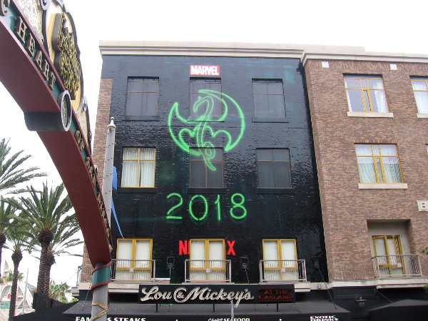 The symbol for Marvel hero Iron Fist in a building wrap near the Gaslamp Quarter landmark sign.