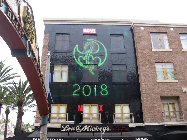The symbol for Marvel hero Iron Fist in a building wrap near the Gaslamp Quarter landmark sign.