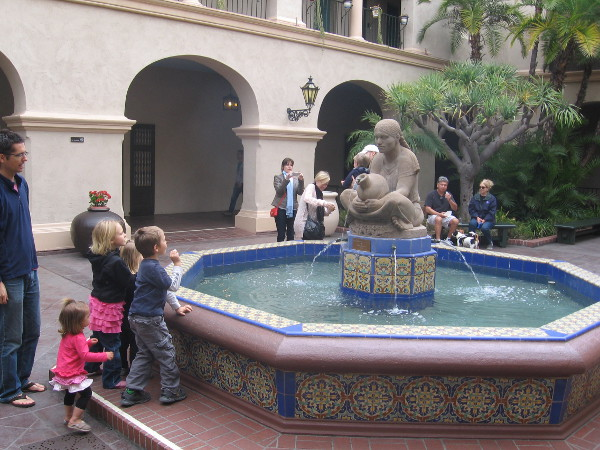 Children gaze at the beautiful fountain and sculpture Woman of Tehuantepec by Donal Hord, in the courtyard of Balboa Park's House of Hospitality.