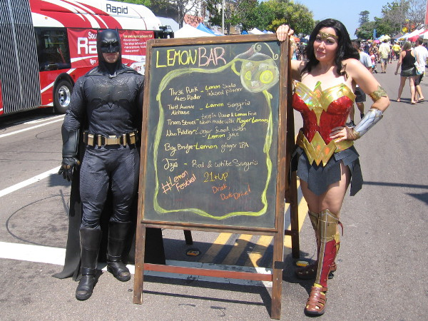 Batman and Wonder Woman dropped on by and posed for a photo by the Lemon Bar sign.