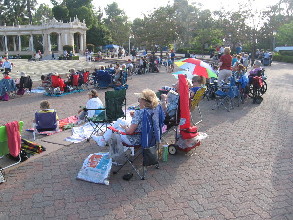 Lots of people have already staked out their spots on benches and lawn chairs over an hour before the program begins.
