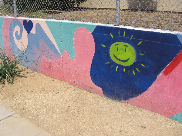 Happy sun painted on a long colorful wall at Perkins Elementary School.