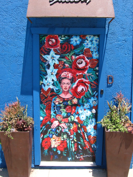 A very flowery Frida Kahlo, painted on a door at The iN Gallery.