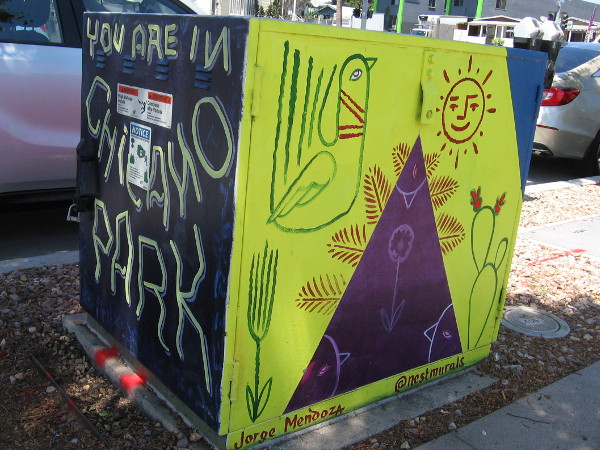 Symbols fill one side of an electrical box. You are in Chicano Park.