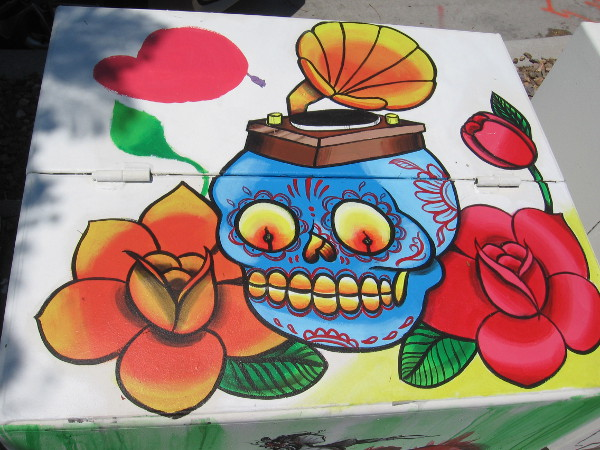 A painted calavera among flowers, topped with a hat-like gramophone.