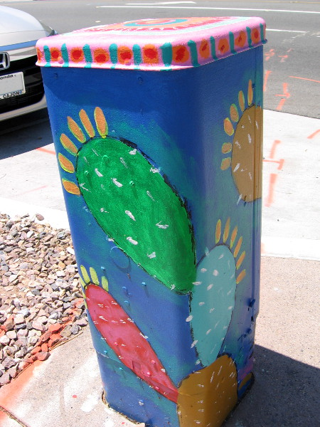 Colorful prickly pears decorate one utility box.