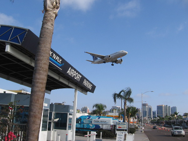 An airplane comes in for a landing at San Diego International Airport near the intersection of Pacific Highway and Laurel Street.