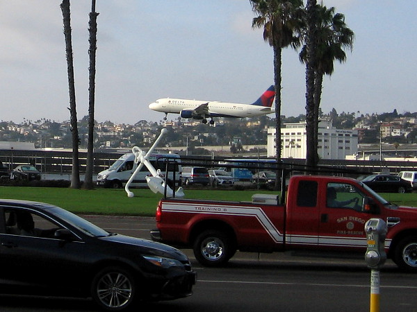 A plane lands at San Diego International Airport, just beyond a large white anchor at Harbor Drive and Laurel Street.