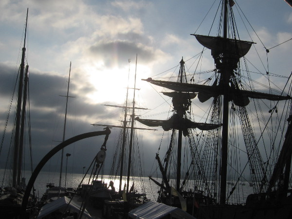 The sun shines out from behind clouds, and the masts of America, Californian and San Salvador.