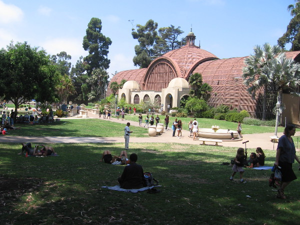 People relax and picnic on the lawn near the Botanical Building.