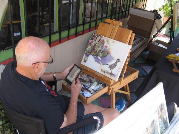A painter creates new artwork outside the window of the Southwestern Artists' Association Gallery in Studio 23.