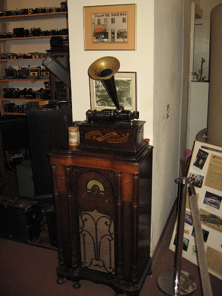 An old photo of the Frank The Train Man storefront over an Edison Home Phonograph.