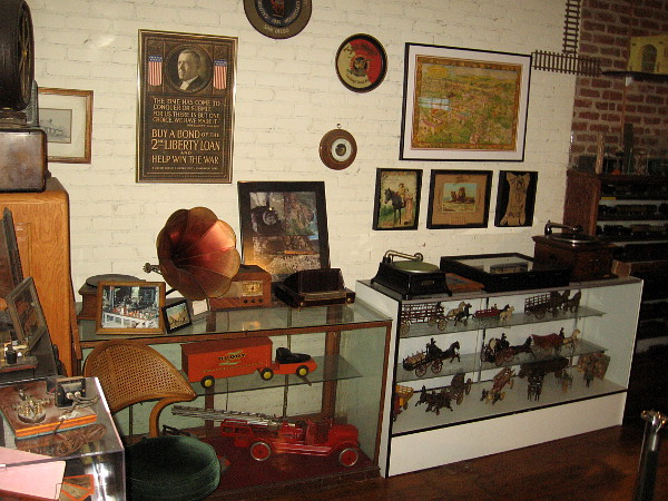One wall and a couple of glass display cases filled with fantastic old collectibles and Americana.