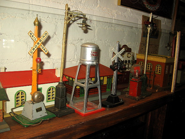 Lionel toy train accessories including buildings and railroad crossing signals.