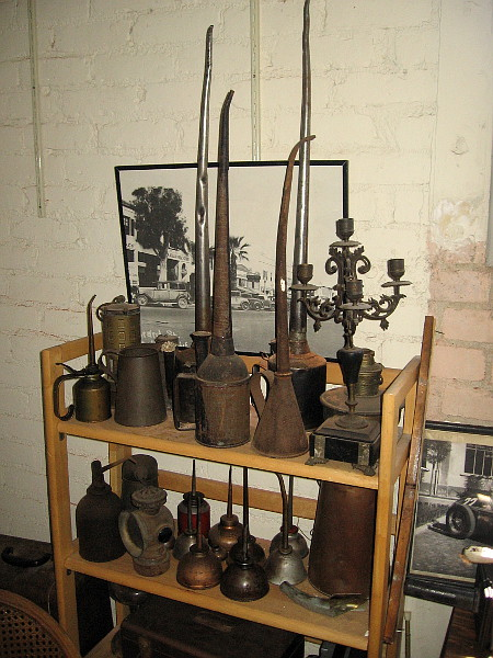 A bunch of old-fashioned oil cans and various other objects.