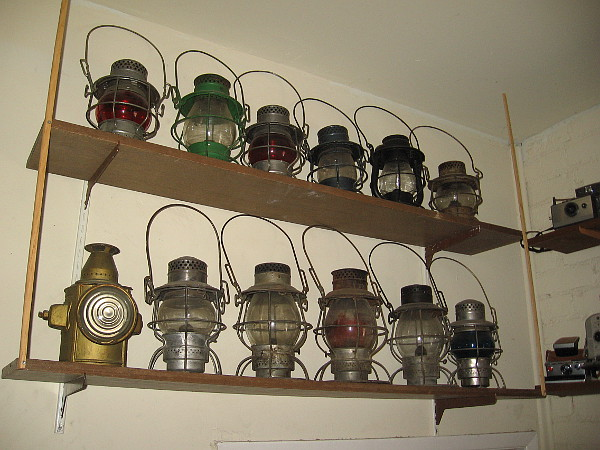 Two shelves containing railroad lanterns.
