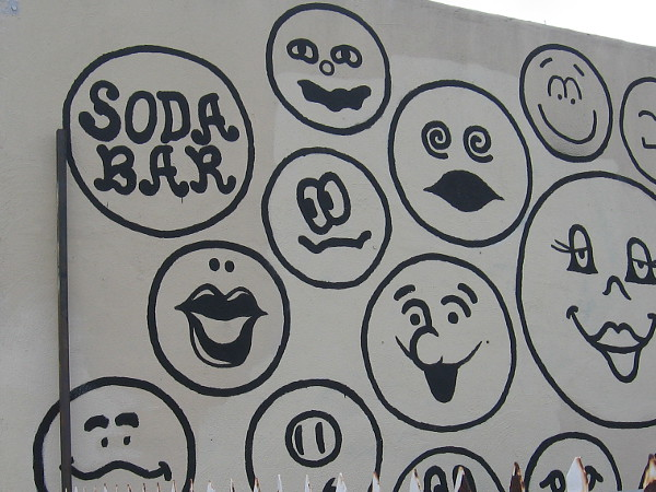 Fun emoji-like faces on the wall of the Soda Bar in City Heights.
