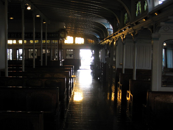 Splashes of sunlight reflect from the floor, woodwork and empty benches inside the passenger deck of Berkeley.